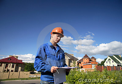 Man with the plan of construction and helmets