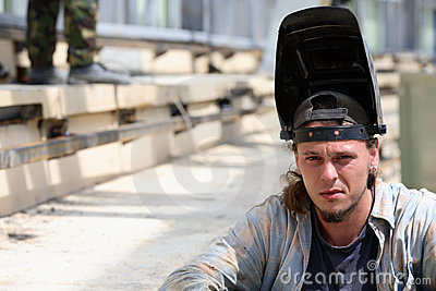 Tired welder sit on stairs