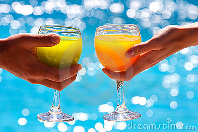 Two glasses with juice against blue water