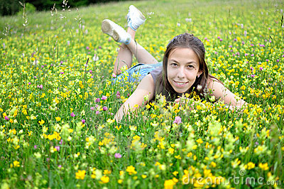 Smiling girl resting on the green grass and flower