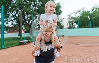 Small kid, a little girl sits on the shoulders of mom smiling, laughing, playing, having fun at tennis court.
