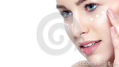 Beautiful Young Blond Woman applying Face cream under her eyes. Facial treatment. Cosmetology, beauty and spa concept