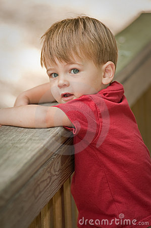 Little boy by fence railing