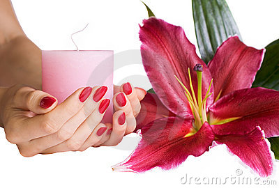 Manicured hands holding a candle