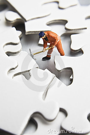 Worker figurine on puzzle pieces