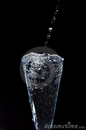 Glass with fresh mineral water on black background