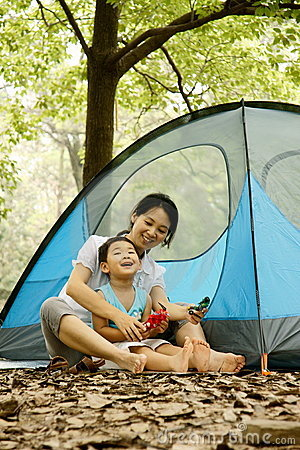 Boy and mother sitting by camp