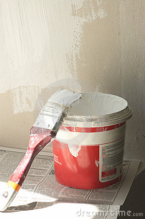 Brush lean on pot with white paint
