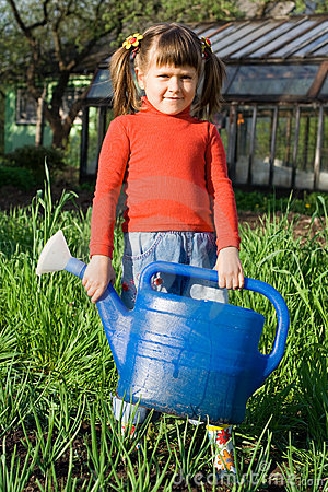 Girl with watering can on the vegetable garden