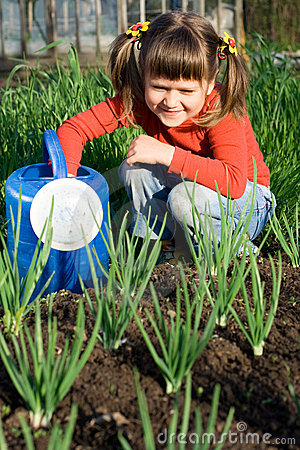Girl with watering can is sitting near onion patch