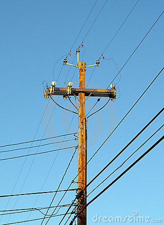 Wooden Telephone pole power pole against blue sky