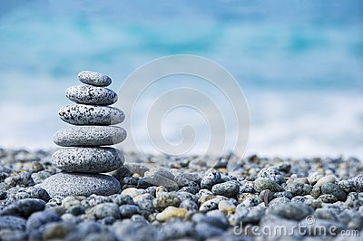 Stones pyramid on pebble beach symbolizing spa concept with blur sea background