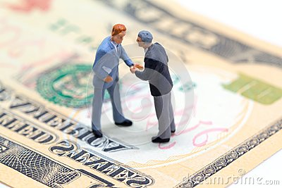 Handshaking businessmen on usa dollar banknote. Business company profitable deal.