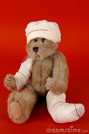 Teddy bear with bandages on red background