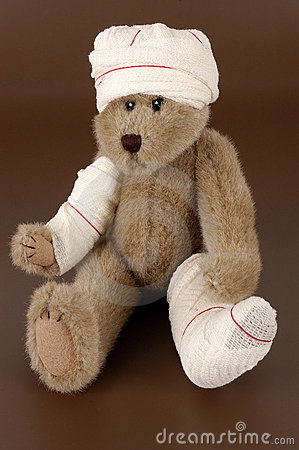Bandaged teddy bear on brown background