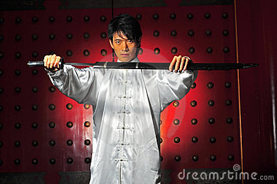 Asian Man Unsheading A Sword