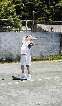Senior tennis player serving ball