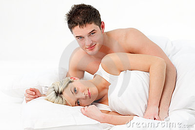 Young couple lying on bed and smiling at the camer