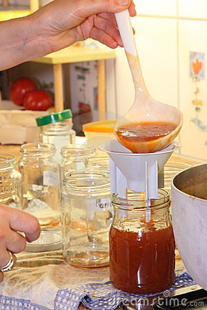 Person filling jars with jam