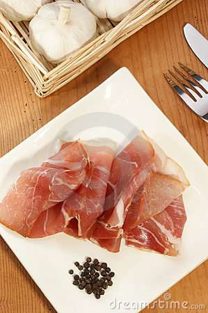 ham on a white plate with fork and knife