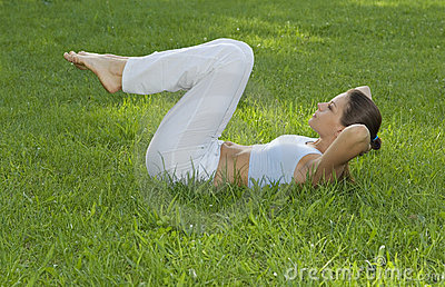Sporty girl exercising on meadow against the sky