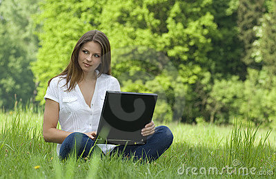 Girl with laptop relaxing on the grass