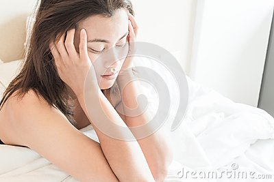 Closeup woman waking up with sore head on bed, health care and m