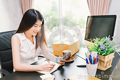 Asian small business owner work at home office, using mobile phone call, writing confirm purchase order on notebook