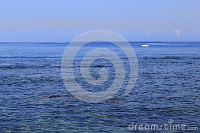 Small white boat adrift in a big blue sea