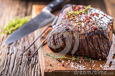 Beef steak. Juicy Rib Eye steak in pan on wooden board with herb and pepper