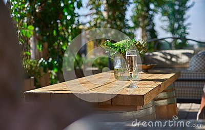 Cozy terrace with sofas for rest, Glass with champagne on a wooden table.