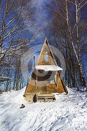 Little wooden house in a snowy winter forest in the mountains in a frosty Sunny day. Tourist resort, Lago-Naki, Adygeya Republic