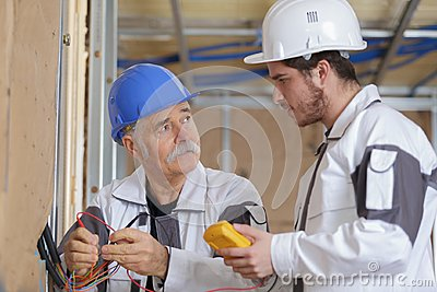 Builders using yellow multimeter to calibrate house