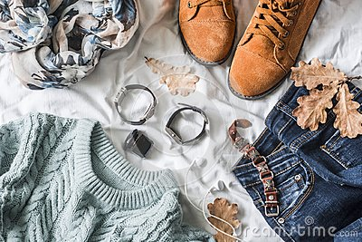 Flat lay women`s clothing for autumn walks, top view. Brown suede boots, jeans, a blue pullover, scarf, bracelets, watches, headp