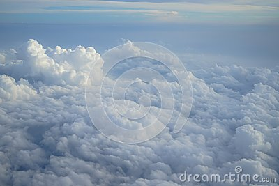Shades of light blue color sky and constantly change floating white cloudscape view from airplane window