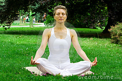 Blonde girl in park doing yoga