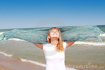 Happy smilling girl at the beach with scarf