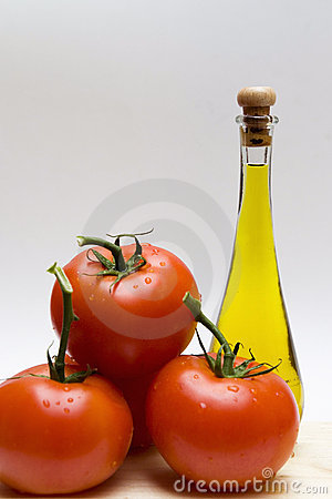 Bottle of oil and three tomatoes