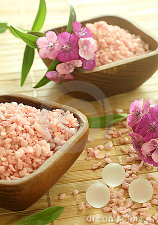 Pink bath salts in wooden bowls and flowers.