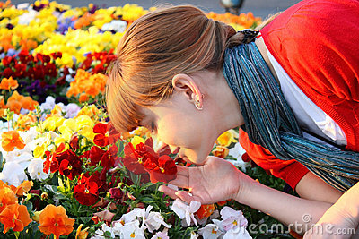 Cute girl sniffing flowers at the sunset
