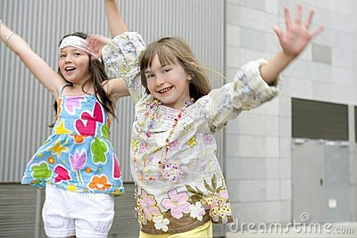 Two little girls dancing in the city