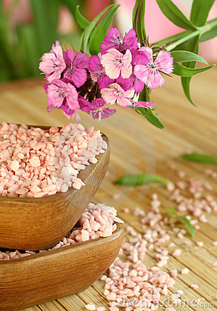 Bath salt in wooden bowl and pink flowers.