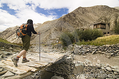 Hiker crossing a bridge in Markha valley, India