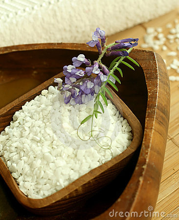 Bath salt in wooden bowl and flowers.