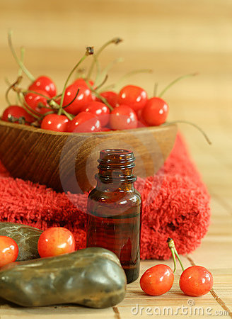 bottle of essence oil, fresh cherry and red towel