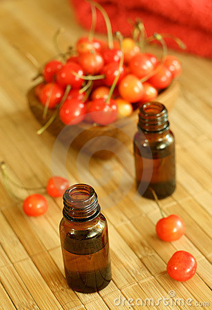 Two bottles of essence oil and fresh cherry
