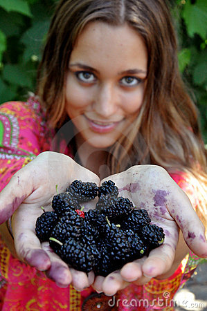 Girl holding out hands with berries