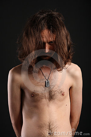 Portrait of young man hiding behind his long hair