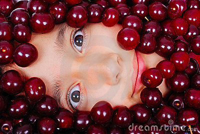A cute girl under many pieces of cherry