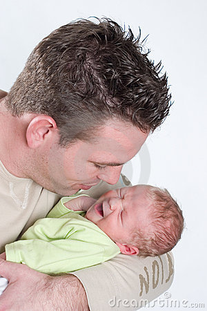 Newborn baby crying in the arms of his papa